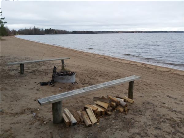 Eldstad och sittbänkar på sandstranden
