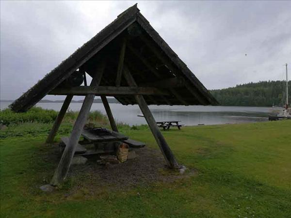 Badstranden syns i bakgrunden. Taket över bord/eldstad skyddar mot regn.