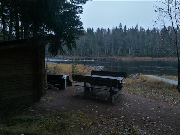 Vindskydd, eldstad och bänkbord som ligger med utsikt över forsen