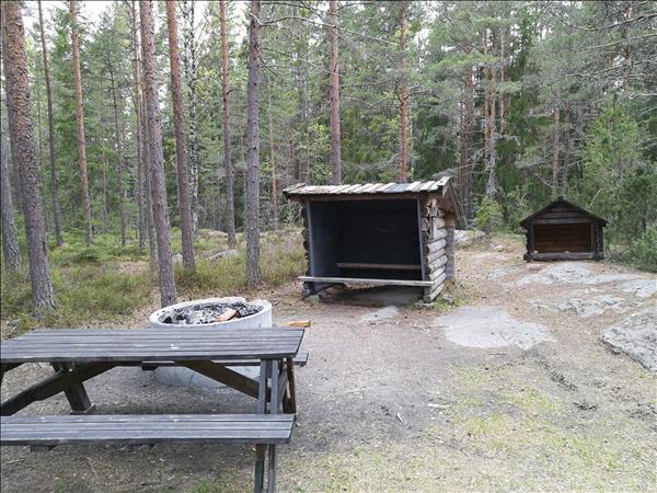 Bänkbord och eldstad med galler finns vid vindskyddet
