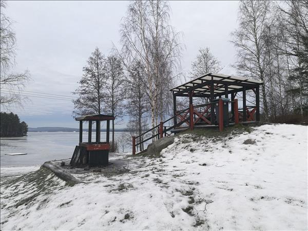 Eldstaden och de regnskyddade sittplatserna ligger på en liten kulle med utsikt över stranden