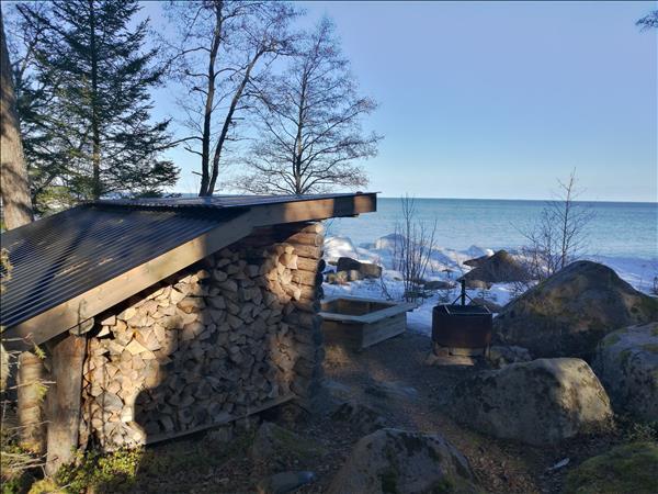Vindskydd liggermed utsikt ut över öppet vatten.
