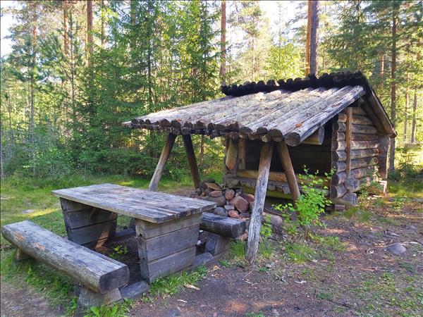 Slogbod med eldstad under tak och bänkbord framför