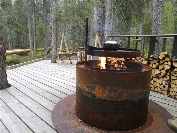 Eldstaden är i mitten av trädäcket med det halvmåneformade vedförrådet till höger