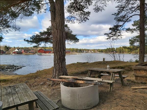 Eldstad och bänkbord med utsikt mot fiskrökeriet på andra sidan