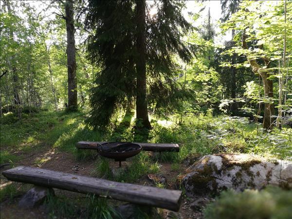 Stilren eldstad i järn med två bänkar på sidorna