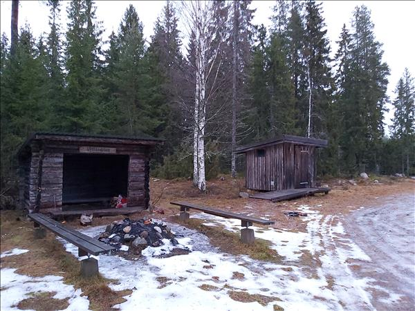 Vindskyddet med eldstad och utedasset i bakgrunden